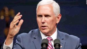 Mike Pence wearing a suit and tie talking on a cell phone