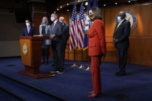 a group of people standing in a room: Speaker Nancy Pelosi of San Francisco listens to a question during a news conference with other Democratic leaders on Tuesday. (Patrick Semansky / Associated Press )